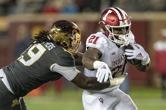 Oct 26, 2018; Minneapolis, MN, USA; Indiana Hoosiers running back Stevie Scott (21) rushes with the ball past Minnesota Golden Gophers defensive lineman Gary Moore (19) in the first quarter at TCF Bank Stadium. Mandatory Credit: Jesse Johnson-USA TODAY Sports