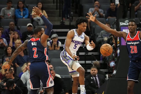 Oct 26, 2018; Sacramento, CA, USA; Sacramento Kings guard De'Aaron Fox (5) passes the ball between Washington Wizards guard John Wall (2) and center Ian Mahinmi (28) during the first quarter at Golden 1 Center. Mandatory Credit: Kelley L Cox-USA TODAY Sports