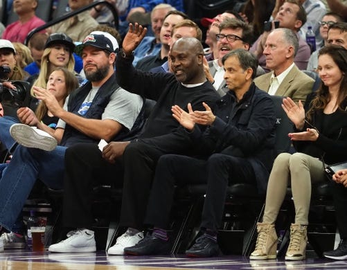 Oct 26, 2018; Sacramento, CA, USA; Retired NBA player Gary Payton Sr. waves as he is acknowledged sitting court side between former Sacramento Kings players Brad Miller and majority owner Vivek Ranadive during the second quarter against the Washington Wizards at Golden 1 Center. Mandatory Credit: Kelley L Cox-USA TODAY Sports