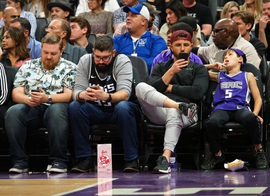 Oct 26, 2018; Sacramento, CA, USA; Courtside fans on their mobile devices next to young Sacramento Kings fan without a mobile device during the second quarter against the Washington Wizards at Golden 1 Center. Mandatory Credit: Kelley L Cox-USA TODAY Sports