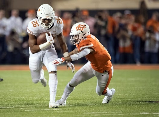 Oct 27, 2018; Stillwater, OK, USA; Texas Longhorns running back Keaontay Ingram (26) runs the ball defended by Oklahoma State Cowboys linebacker Kenneth Edison-McGruder (3) during the first quarter at Boone Pickens Stadium. Mandatory Credit: Rob Ferguson-USA TODAY Sports