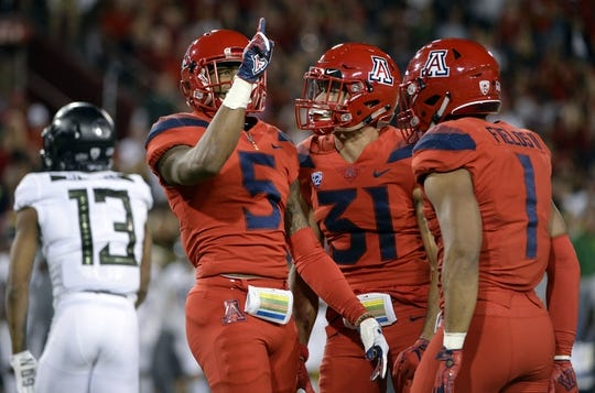 Oct 27, 2018; Tucson, AZ, USA; Arizona Wildcats safety Christian Young (5) safety Tristan Cooper (31) and linebacker Tony Fields II (1) celebrate after making a stop against the Oregon Ducks during the first half at Arizona Stadium. Mandatory Credit: Casey Sapio-USA TODAY Sports