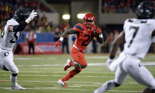Oct 27, 2018; Tucson, AZ, USA; Arizona Wildcats running back J.J. Taylor (21) runs the ball during the second half against the Oregon Ducks at Arizona Stadium. Mandatory Credit: Casey Sapio-USA TODAY Sports