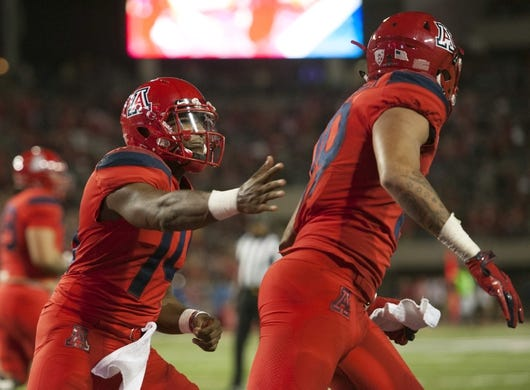 Oct 27, 2018; Tucson, AZ, USA; Arizona Wildcats quarterback Khalil Tate (14) (left) and wide receiver Shawn Poindexter (19) celebrate after scoring a touchdown against the Oregon Ducks during the second half at Arizona Stadium. Mandatory Credit: Casey Sapio-USA TODAY Sports