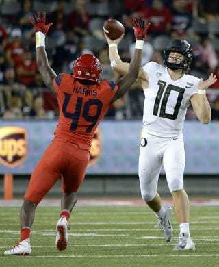 Oct 27, 2018; Tucson, AZ, USA; Oregon Ducks quarterback Justin Herbert (10) passes the ball as Arizona Wildcats defensive end Jalen Harris (49) defends during the second half at Arizona Stadium. Mandatory Credit: Casey Sapio-USA TODAY Sports