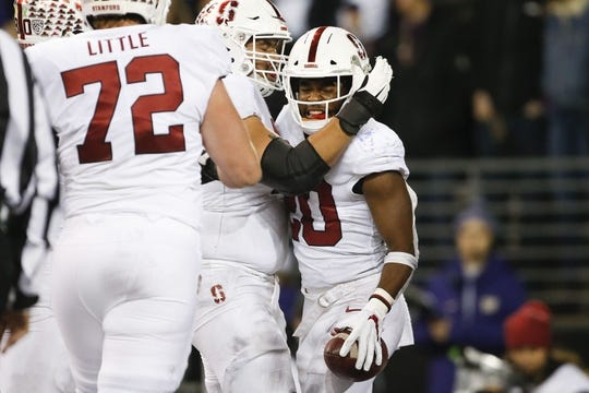 Nov 3, 2018; Seattle, WA, USA; Stanford Cardinal running back Bryce Love (20) celebrates with his offensive line after a touchdown against the Washington Huskies during the third quarter at Husky Stadium. Mandatory Credit: Jennifer Buchanan-USA TODAY Sports