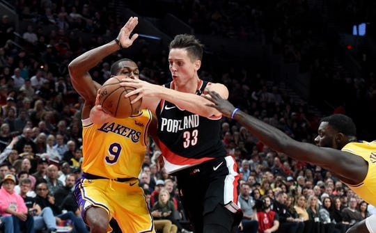 Nov 3, 2018; Portland, OR, USA; Portland Trail Blazers forward Zach Collins (33) drives to the basket on Los Angeles Lakers guard Rajon Rondo (9) as guard Lance Stephenson (6) reaches in during the second half of the game at the Moda Center. The Lakers won the game 114-110. Mandatory Credit: Steve Dykes-USA TODAY Sports