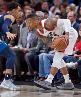 Nov 4, 2018; Portland, OR, USA; Portland Trail Blazers guard Damian Lillard (0) looks past Minnesota Timberwolves guard Tyus Jones (1) during the first quarter at the Moda Center. Mandatory Credit: Craig Mitchelldyer-USA TODAY Sports