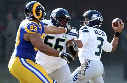 November 11, 2018; Los Angeles, CA, USA; Seattle Seahawks quarterback Russell Wilson (3) throws as linebacker Mychal Kendricks (56) blocks against Los Angeles Rams nose tackle Ndamukong Suh (93) during the first half at the Los Angeles Memorial Coliseum. Mandatory Credit: Gary A. Vasquez-USA TODAY Sports