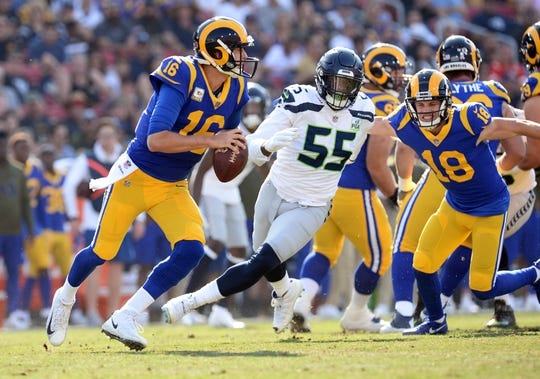 November 11, 2018; Los Angeles, CA, USA; Los Angeles Rams quarterback Jared Goff (16) rolls out to pass as Seattle Seahawks defensive end Frank Clark (55) moves in during the first half at the Los Angeles Memorial Coliseum. Mandatory Credit: Gary A. Vasquez-USA TODAY Sports