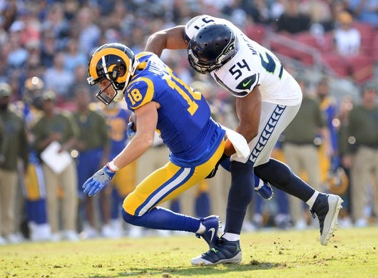 November 11, 2018; Los Angeles, CA, USA; Los Angeles Rams wide receiver Cooper Kupp (18) is brought dow by Seattle Seahawks middle linebacker Bobby Wagner (54) during the first half at the Los Angeles Memorial Coliseum. Mandatory Credit: Gary A. Vasquez-USA TODAY Sports