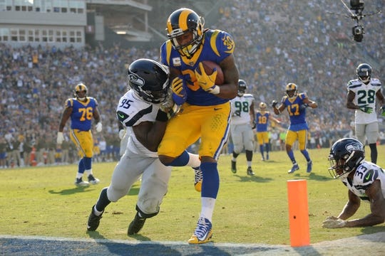 November 11, 2018; Los Angeles, CA, USA; Los Angeles Rams running back Todd Gurley (30) runs in for a touchdown against Seattle Seahawks defensive end Dion Jordan (95) and free safety Tedric Thompson (33) during the first half at the Los Angeles Memorial Coliseum. Mandatory Credit: Gary A. Vasquez-USA TODAY Sports