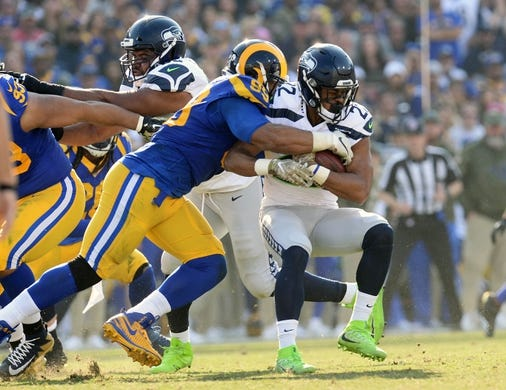 November 11, 2018; Los Angeles, CA, USA; Seattle Seahawks running back C.J. Prosise (22) is brought down by Los Angeles Rams defensive end Aaron Donald (99) during the first half at the Los Angeles Memorial Coliseum. Mandatory Credit: Gary A. Vasquez-USA TODAY Sports