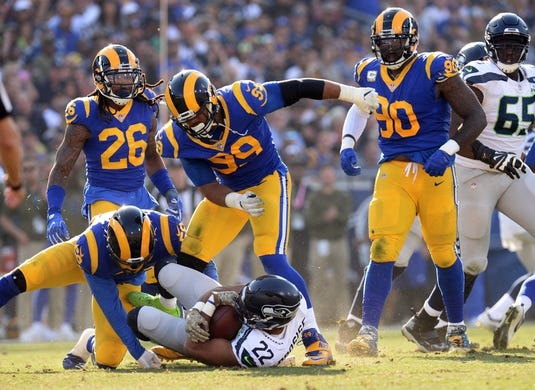 November 11, 2018; Los Angeles, CA, USA; Seattle Seahawks running back C.J. Prosise (22) is brought down by Los Angeles Rams defensive end Aaron Donald (99) and linebacker Micah Kiser (59) during the first half at the Los Angeles Memorial Coliseum. Mandatory Credit: Gary A. Vasquez-USA TODAY Sports