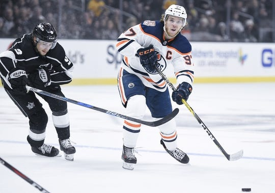 Nov 25, 2018; Los Angeles, CA, USA; Edmonton Oilers center Connor McDavid (97) passes the puck while Los Angeles Kings right wing Adrian Kempe (9) defends during the first period at Staples Center. Mandatory Credit: Kelvin Kuo-USA TODAY Sports