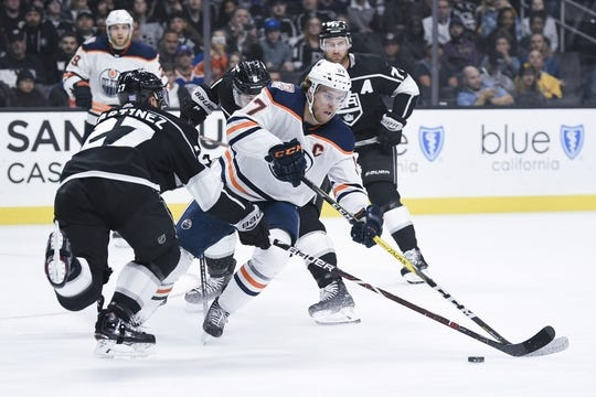 Nov 25, 2018; Los Angeles, CA, USA; Edmonton Oilers center Connor McDavid (97) moves the puck while Los Angeles Kings defenseman Alec Martinez (27) defends during the first period at Staples Center. Mandatory Credit: Kelvin Kuo-USA TODAY Sports