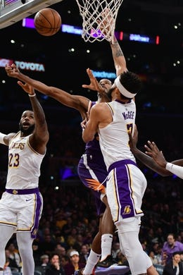 Dec 2, 2018; Los Angeles, CA, USA; Phoenix Suns forward Trevor Ariza (3) puts up a shot between Los Angeles Lakers forward LeBron James (23) and Los Angeles Lakers center JaVale McGee (7) during the first quarter at Staples Center. Mandatory Credit: Robert Hanashiro-USA TODAY Sports