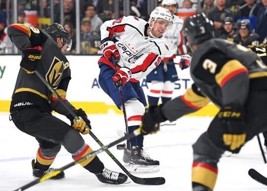 Dec 4, 2018; Las Vegas, NV, USA; Washington Capitals center Evgeny Kuznetsov (92) flips a pass between two Vegas Golden Knights players during the first period at T-Mobile Arena. Mandatory Credit: Stephen R. Sylvanie-USA TODAY Sports