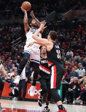 Dec 8, 2018; Portland, OR, USA;  Minnesota Timberwolves guard Derrick Rose (25) shoots over Portland Trail Blazers forward Zach Collins (33) in the first half at Moda Center. Mandatory Credit: Jaime Valdez-USA TODAY Sports