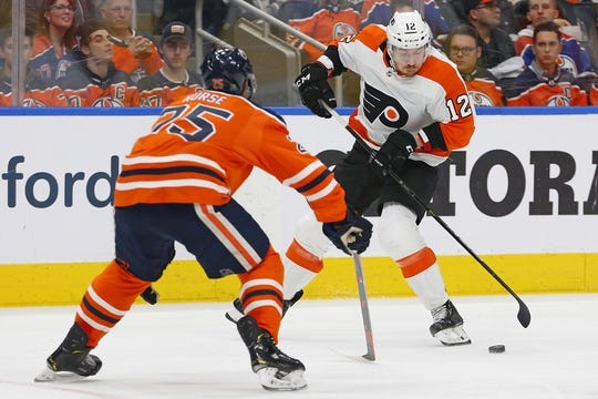 Dec 14, 2018; Edmonton, Alberta, CAN; Philadelphia Flyers forward Michael Raffl (12) tires to carry the puck around Edmonton Oilers defensemen Darnell Nurse (25) during the second period at Rogers Place. Mandatory Credit: Perry Nelson-USA TODAY Sports