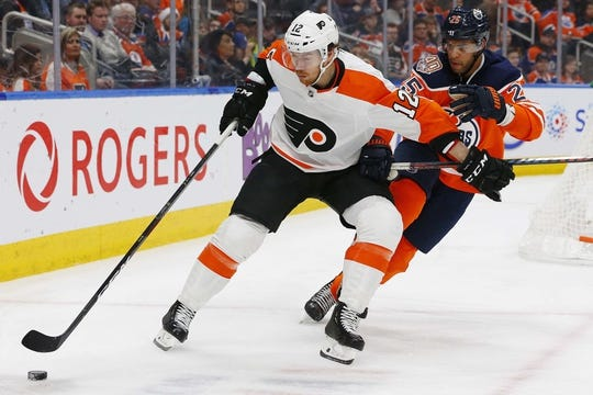Dec 14, 2018; Edmonton, Alberta, CAN; Edmonton Oilers defensemen Darnell Nurse (25) tries to check Philadelphia Flyers forward Michael Raffl (12) during the second period  at Rogers Place. Mandatory Credit: Perry Nelson-USA TODAY Sports