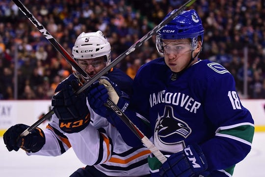 Dec 16, 2018; Vancouver, British Columbia, CAN; Edmonton Oilers defenseman Kevin Gravel (5) battles for the puck against Vancouver Canucks forward Jake Virtanen (18) during the first period at Rogers Arena. Mandatory Credit: Anne-Marie Sorvin-USA TODAY Sports