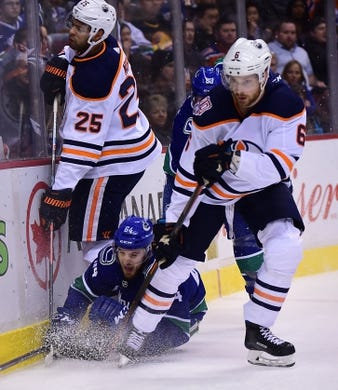 Dec 16, 2018; Vancouver, British Columbia, CAN; Edmonton Oilers defenseman Darnell Nurse (25) and defenseman Adam Larsson (6) defend against Vancouver Canucks forward Tyler Motte (64)  the first period at Rogers Arena. Mandatory Credit: Anne-Marie Sorvin-USA TODAY Sports