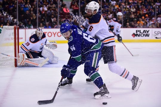Dec 16, 2018; Vancouver, British Columbia, CAN; Vancouver Canucks forward Tyler Motte (64) battles for the puck against Edmonton Oilers defenseman Adam Larsson (6) during the first period at Rogers Arena. Mandatory Credit: Anne-Marie Sorvin-USA TODAY Sports