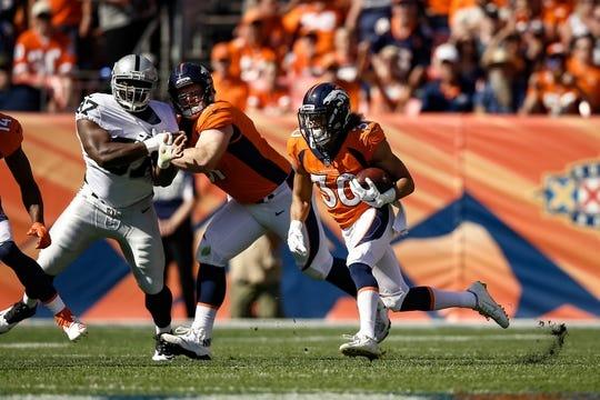 Sep 16, 2018; Denver, CO, USA; Denver Broncos running back Phillip Lindsay (30) runs the ball as center Matt Paradis (61) defends against Oakland Raiders defensive tackle Clinton McDonald (97) in the second quarter at Broncos Stadium at Mile High. Mandatory Credit: Isaiah J. Downing-USA TODAY Sports
