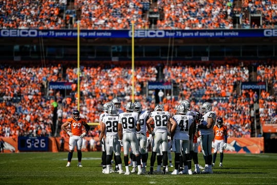 Sep 16, 2018; Denver, CO, USA; Denver Broncos defensive end Adam Gotsis (99) looks on as running back Doug Martin (28) and wide receiver Amari Cooper (89) and wide receiver Jordy Nelson (82) and fullback Keith Smith (41) talk with teammates during a stoppage of play in the second quarter at Broncos Stadium at Mile High. Mandatory Credit: Isaiah J. Downing-USA TODAY Sports