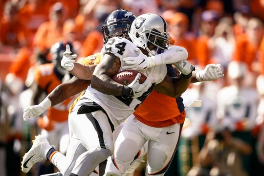 Sep 16, 2018; Denver, CO, USA; Oakland Raiders running back Marshawn Lynch (24) is tackled by Denver Broncos inside linebacker Brandon Marshall (54) in the second quarter at Broncos Stadium at Mile High. Mandatory Credit: Isaiah J. Downing-USA TODAY Sports