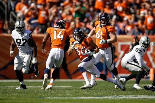 Sep 16, 2018; Denver, CO, USA; Denver Broncos running back Phillip Lindsay (30) runs the ball as wide receiver Courtland Sutton (14) and center Matt Paradis (61) defend against Oakland Raiders defensive tackle Clinton McDonald (97) and safety Reggie Nelson (27) in the second quarter at Broncos Stadium at Mile High. Mandatory Credit: Isaiah J. Downing-USA TODAY Sports