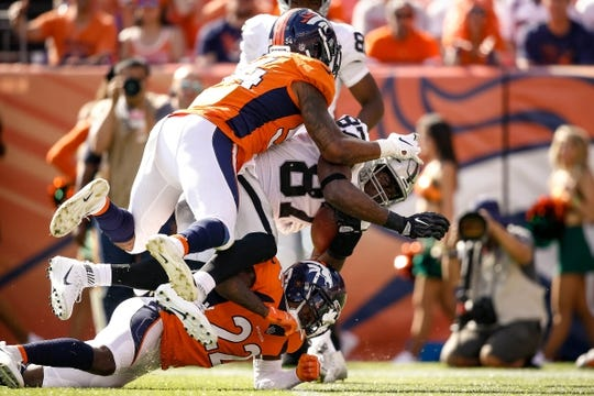 Sep 16, 2018; Denver, CO, USA; Oakland Raiders tight end Jared Cook (87) is tackled by Denver Broncos cornerback Tramaine Brock (22) and inside linebacker Brandon Marshall (54) in the second quarter at Broncos Stadium at Mile High. Mandatory Credit: Isaiah J. Downing-USA TODAY Sports