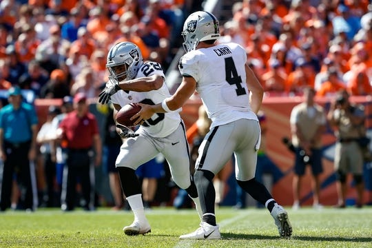Sep 16, 2018; Denver, CO, USA; Oakland Raiders quarterback Derek Carr (4) hands the ball off to running back Doug Martin (28) in the first quarter against the Denver Broncos at Broncos Stadium at Mile High. Mandatory Credit: Isaiah J. Downing-USA TODAY Sports