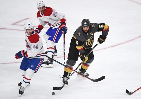 Dec 22, 2018; Las Vegas, NV, USA; Vegas Golden Knights defenseman Deryk Engelland (5) takes a shot behind Montreal Canadiens center Phillip Danault (24) and defenseman Jeff Petry (26) during the first period at T-Mobile Arena. Mandatory Credit: Stephen R. Sylvanie-USA TODAY Sports
