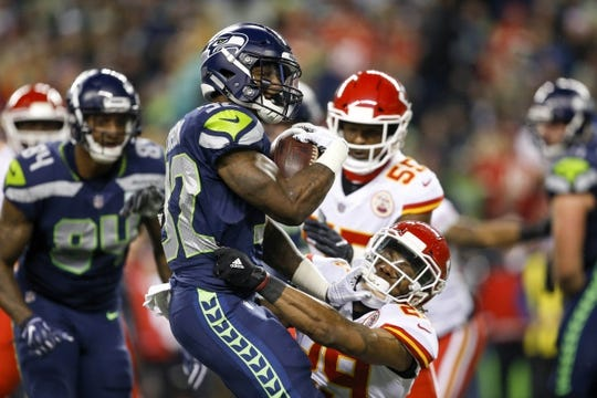 Dec 23, 2018; Seattle, WA, USA; Seattle Seahawks running back Chris Carson (32) is tackled by Kansas City Chiefs defensive back Eric Berry (29) during the first quarter at CenturyLink Field. Mandatory Credit: Joe Nicholson-USA TODAY Sports