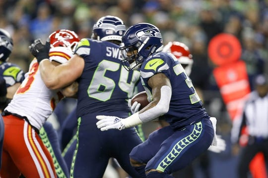 Dec 23, 2018; Seattle, WA, USA; Seattle Seahawks running back Chris Carson (32) rushes against the Kansas City Chiefs during the first quarter at CenturyLink Field. Mandatory Credit: Joe Nicholson-USA TODAY Sports