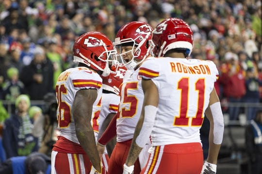 Dec 23, 2018; Seattle, WA, USA; Kansas City Chiefs running back Damien Williams (26) and quarterback Patrick Mahomes (15) and wide receiver Demarcus Robinson (11) celebrate after Williams scored a touchdown against the Seattle Seahawks during the first half at CenturyLink Field. Mandatory Credit: Steven Bisig-USA TODAY Sports