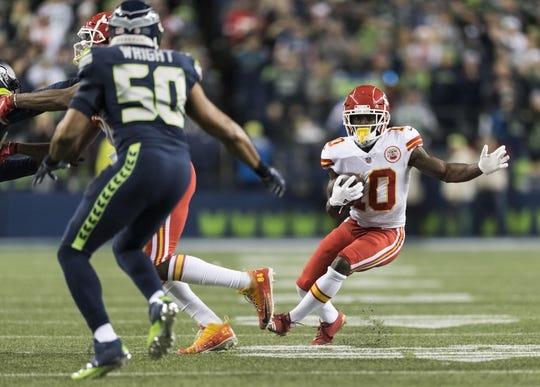 Dec 23, 2018; Seattle, WA, USA; Kansas City Chiefs wide receiver Tyreek Hill (10) carries the ball after making a catch against the Seattle Seahawks during the first half at CenturyLink Field. Mandatory Credit: Steven Bisig-USA TODAY Sports