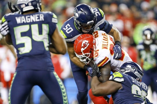 Dec 23, 2018; Seattle, WA, USA; Seattle Seahawks outside linebacker K.J. Wright (50) and defensive tackle Shamar Stephen (98) tackle Kansas City Chiefs running back Damien Williams (26) during the second quarter at CenturyLink Field. Mandatory Credit: Joe Nicholson-USA TODAY Sports