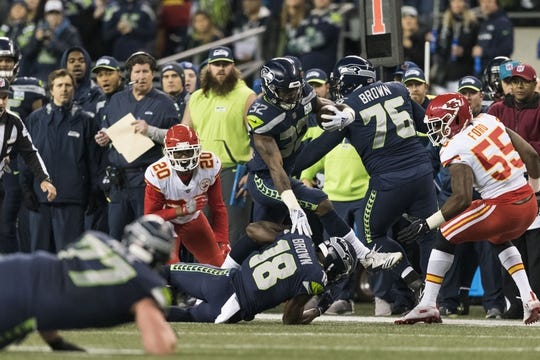 Dec 23, 2018; Seattle, WA, USA; Seattle Seahawks running back Chris Carson (32) jumps over Seattle Seahawks wide receiver Jaron Brown (18) during a run play against the Kansas City Chiefs during the first half at CenturyLink Field. Seattle defeated Kansas City 38-31. Mandatory Credit: Steven Bisig-USA TODAY Sports