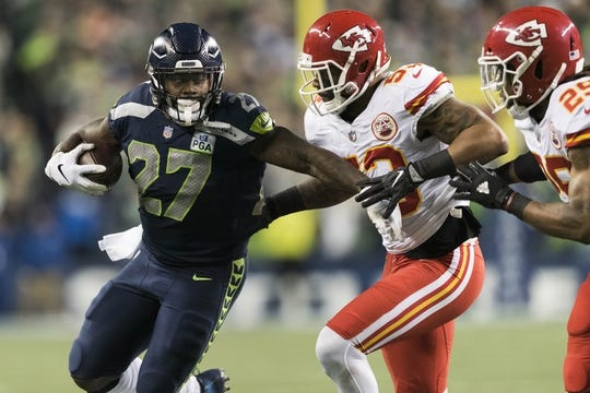 Dec 23, 2018; Seattle, WA, USA; Seattle Seahawks running back Mike Davis (27) carries the ball while being defended by Kansas City Chiefs inside linebacker Anthony Hitchens (53) during the first half at CenturyLink Field. Seattle defeated Kansas City 38-31. Mandatory Credit: Steven Bisig-USA TODAY Sports