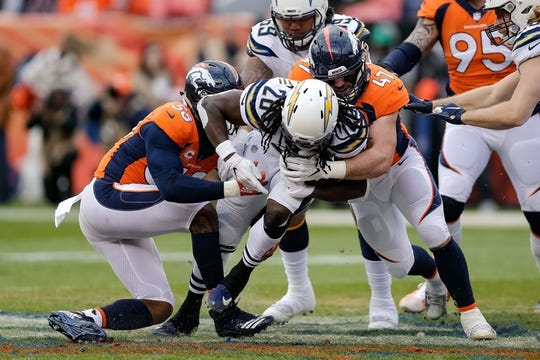 Dec 30, 2018; Denver, CO, USA; Los Angeles Chargers running back Melvin Gordon (28) is tackled by Denver Broncos inside linebacker Josey Jewell (47) and outside linebacker Von Miller (58) in the first quarter at Broncos Stadium at Mile High. Mandatory Credit: Isaiah J. Downing-USA TODAY Sports