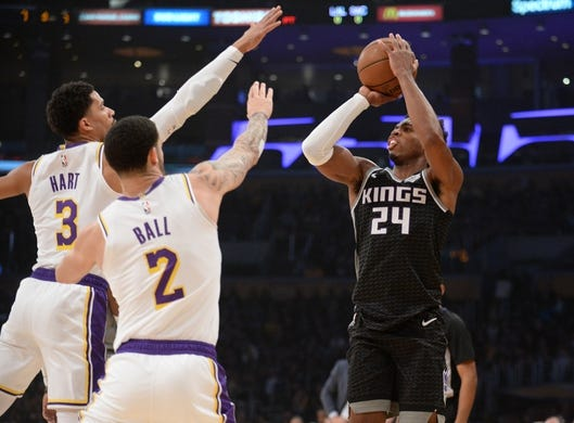December 30, 2018; Los Angeles, CA, USA; Sacramento Kings guard Buddy Hield (24) shoots against the defense of Los Angeles Lakers guard Josh Hart (3) and guard Lonzo Ball (2) during the first half at Staples Center. Mandatory Credit: Gary A. Vasquez-USA TODAY Sports