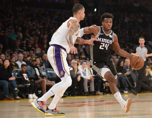 December 30, 2018; Los Angeles, CA, USA; Sacramento Kings guard Buddy Hield (24) moves the ball against Los Angeles Lakers forward Kyle Kuzma (0) during the first half at Staples Center. Mandatory Credit: Gary A. Vasquez-USA TODAY Sports