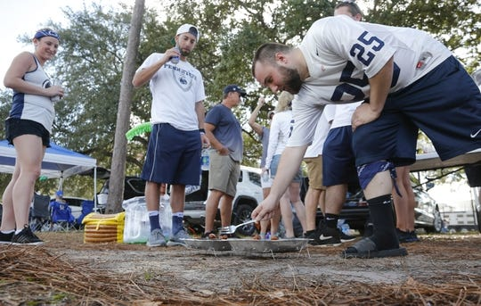 Jan 1, 2019; Orlando, FL, USA; Penn State Nittany Lions fan Brad Basko (right) cooks hotdogs for tailgaters prior to the Nittany Lions game against the Kentucky Wildcats in the 2019 Citrus Bowl at Camping World Stadium. Mandatory Credit: Reinhold Matay-USA TODAY Sports