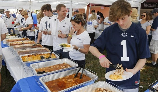 Jan 1, 2019; Orlando, FL, USA; Members of the Penn State Nittany Lions Alumni Association of Central Florida eat at a buffet tent prior to the Nittany Lions game against the Kentucky Wildcats in the 2019 Citrus Bowl at Camping World Stadium. Mandatory Credit: Reinhold Matay-USA TODAY Sports