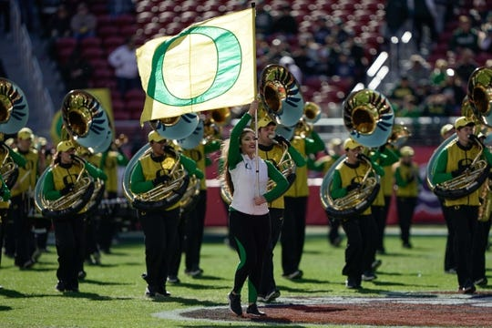 Dec 31, 2018; Santa Clara, CA, USA; Oregon Ducks cheerleader walks with the band before the game against the Michigan State Spartans at Levi's Stadium. Mandatory Credit: Stan Szeto-USA TODAY Sports