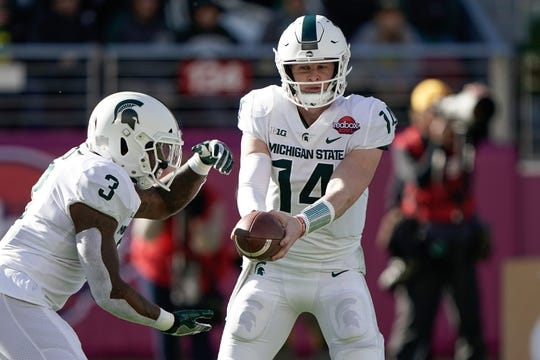 Dec 31, 2018; Santa Clara, CA, USA; Michigan State Spartans quarterback Brian Lewerke (14) looks to hand off the ball to running back LJ Scott (3) during the first quarter at Levi's Stadium. Mandatory Credit: Stan Szeto-USA TODAY Sports