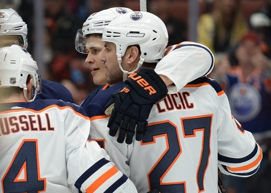 January 6, 2019; Anaheim, CA, USA; Edmonton Oilers right wing Jesse Puljujarvi (98) celebrates with left wing Milan Lucic (27) and defenseman Kris Russell (4) his goal scored against the Anaheim Ducks during the first period at Honda Center. Mandatory Credit: Gary A. Vasquez-USA TODAY Sports